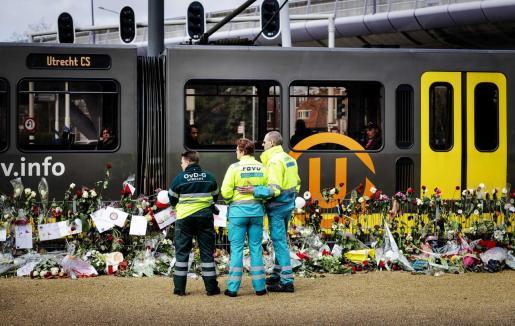 Tres personas observan los ramos de flores y mensajes en memoria de las víctimas en el escenario del tiroteo ocurrido el pasado 18 de marzo.