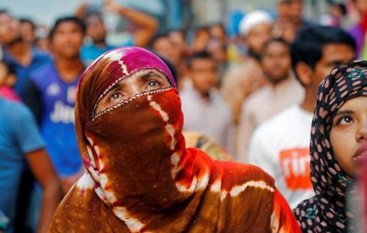 Personas observan el incendio que se ha producido en un edificio, este jueves en Dacca (Bangladesh).