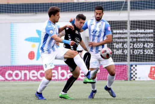 Los jugadores del Atlético Baleares Villapalos y Rubén González intentan frenar a un rival en Son Malferit.