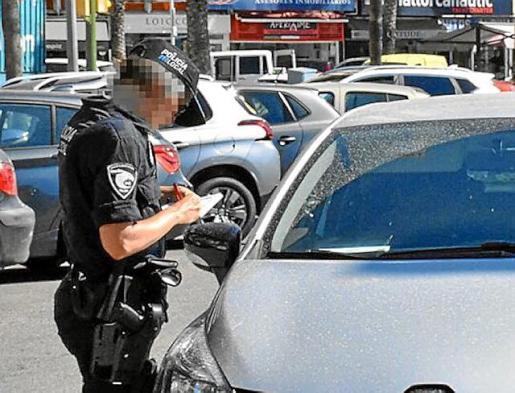 Un agente multa a un coche de alquiler sin contrato.