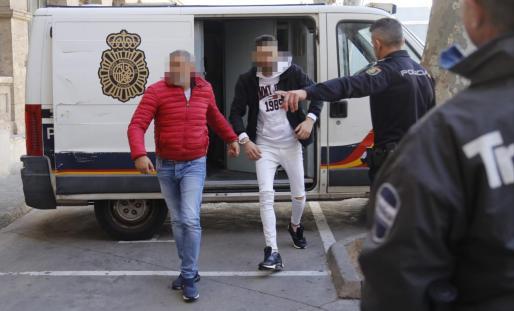 Uno de los detenidos, el de la chaqueta roja, bajando del furgón policial.