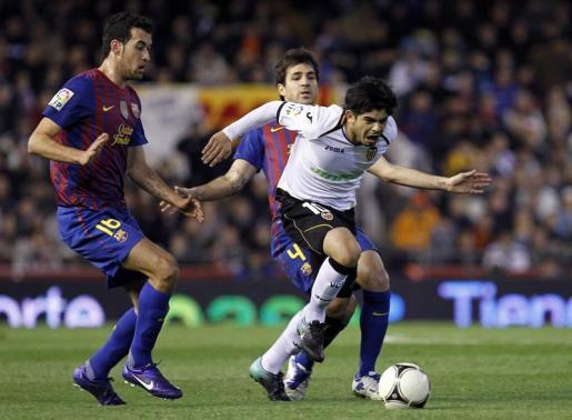 El centrocampista argentino del Valencia Ever Bánega disputa un balón a los jugadores del Barcelona Sergio Busquets (i) y Cesc Fábregas (detrás) durante el partido, correspondiente a la ida de las semifinales de la Copa del Rey.