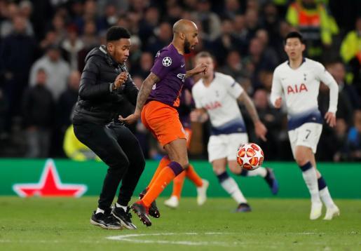 Fabian Delph del Manchester City en acción cuando un espontáneo interrumpe el juego.