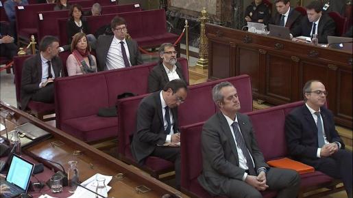 Captura de la señal institucional del Tribunal Supremo este jueves. Jordi Turull, exportavoz y exconsejero de la presidencia (d), y el exconsejero de Interior Joaquim Forn (i), tras la reanudación de la sesión por la indisposición de un auxiliar del Supremo.
