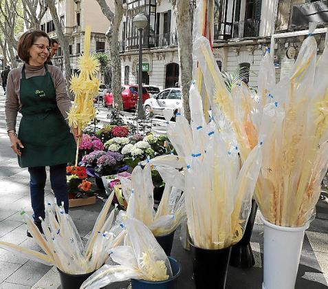 Mercè Zoroa muestra una palma meticulosamente elaborada en su floristería de La Rambla.