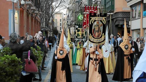 Algunas personas toman imágenes de la procesión a su paso por la calle Colom.