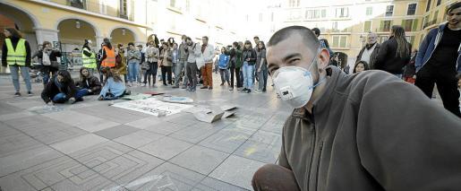 Un manifestante con mascarilla antipolución, durante la concentración de este viernes en la Plaça Major de Palma.