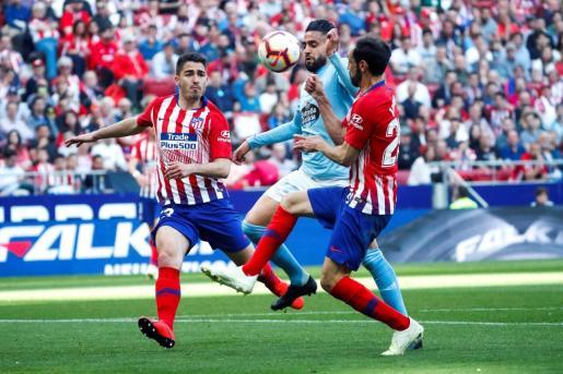 El centrocampista marroquí del Celta de Vigo Sofiane Boufal (c) lucha con Antonio Moya (i) y Juanfran (d), ambos del Atlético de Madrid, durante el partido de la trigésimo segunda jornada de Liga en Primera División que Atlético de Madrid y Celta de Vigo han jugado en el Wanda Metropolitano, en Madrid.