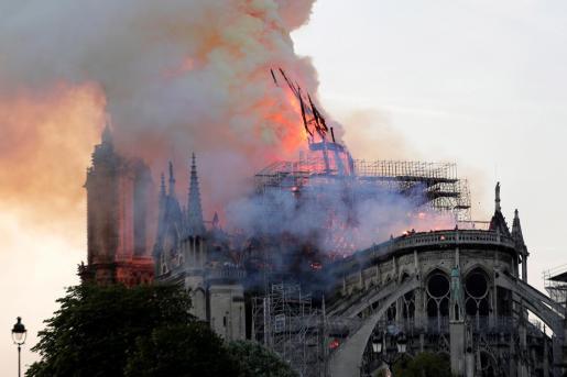 La aguja central de la catedral de Notre Dame cae durante un incendio este lunes en París, Francia.