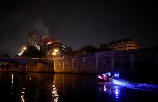 Tareas de extinción durante la noche del fuego que ha consumido buena parte del techo de la catedral parisina.