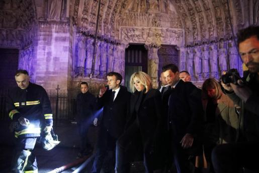 El presidente de Francia, Emmanuel Macron (c), y su esposa Brigitte Macron, cerca del dispositivo de extinción del incendio declarado en la catedral de Notre Dame de París.