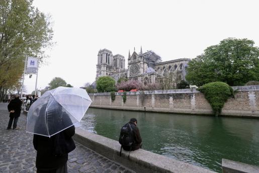 Varios parisinos observan con pesar la silueta de la catedral parisina el día después del incendio.