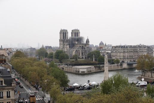 Vista de la estatua de Santa Genoveva (c,delante), patrona de la ciudad, en el puente Pont de la Tournelle, con la catedral de Notre Dame al fondo, este martes en París (Francia).