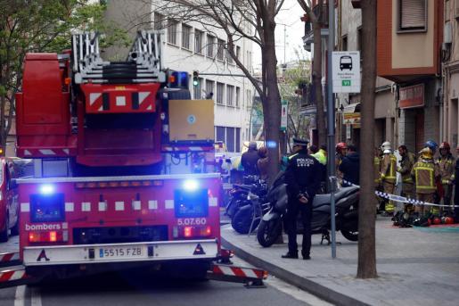 Bomberos y Mossos d'Esquadra permanecen en las inmediaciones del inmueble situado en la calle Riera Blanca de L'Hospitalet de Llobregat (Barcelona) dondese ha declarado el incendio.