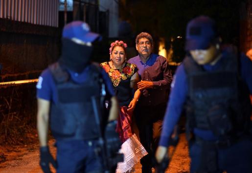 Testigos del ataque acompañan a los policías en el escenario de los asesinatos.