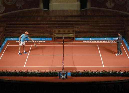 Rafael Nadal pelotea con el tenista japonés Kei Nishikori en una pista de tenis montada en el escenario del Palau de la Música Catalana, durante un acto previo al torneo internacional de tenis Conde de Godo.
