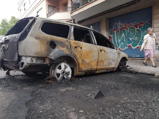 Imagen de un vehículo calcinado por la quema de varios contenedores en la calle Poeta Guillem Colom de Palma.