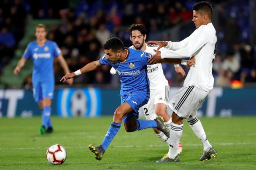 El delantero del Getafe, Ángel Luis Rodríguez (i), intenta llevarse el balón ante el defensa francés del Real Madrid, Raphael Varane, durante el encuentro correspondiente a la jornada 34 de primera división.