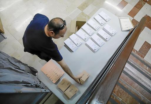 Un operario coloca las papeletas del Senado en una mesa en s'Escorxador. Ayer acabaron los preparativos de los 385 colegios electorales de Balears que suman 1.215 mesas electorales y 2.430 urnas. Los colegios abren hoy a las 9.00 y cierran a las 20.00 horas.