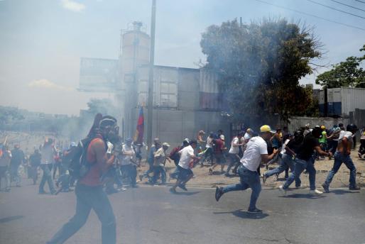 Manifestantes opositores en Caracas dispersados por la policía.