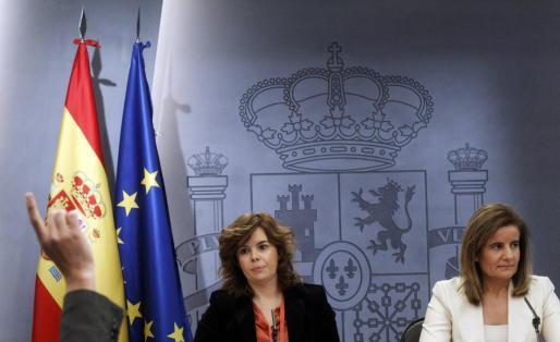 La portavoz del Gobierno, Soraya Saenz de Santamaria (izquierda) y la ministra de Trabajo, Fátima Bañez, en la rueda de prensa en la que han explicado la reforma laboral aprobada hoy en el Congreso.