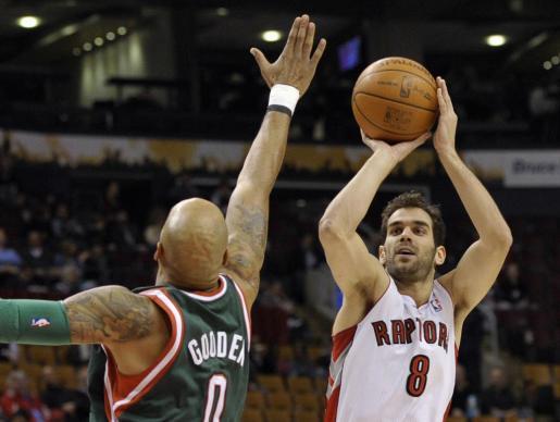 El jugador de los Toronto Raptors José Manuel Calderón tira a canasta ante la defensa de Drew Gooden, de los Milwaukee Bucks.