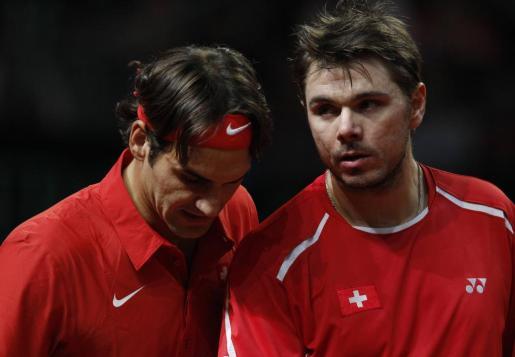 Los suizos Roger Federer y Stanislas Wawrinka reaccionan durante su partido de dobles.