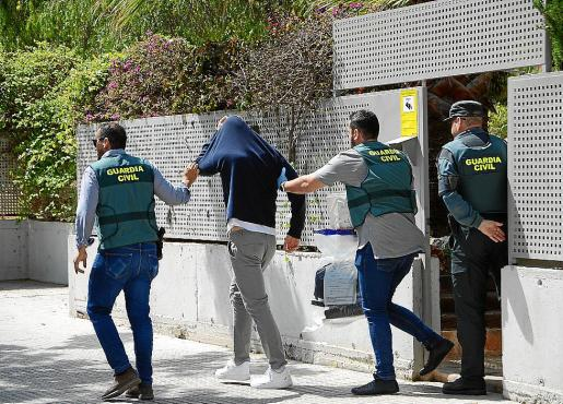 Dos agentes de la Guardia Civil, junto a uno de los detenidos, este jueves en Palmanova.