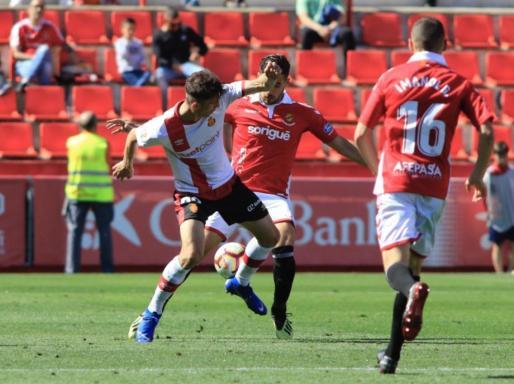 El mallorquinista Ante Budimir intenta proteger el balón ante la presión de dos jugadores del Nàstic de Tarragona.