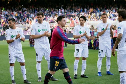 El delantero argentino del FC Barcelona, Lionel Messi (c), pasa delante de los jugadores del Getafe CF que hacen el pasillo al FC Barcelona al proclamarse matemáticamente campeones de liga minutos antes del inicio el encuentro