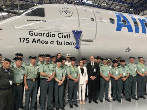 Agentes de la Guardia Civil, frente al avión rotulado por su 175 aniversario.
