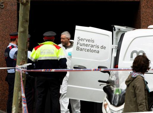 Mossos d'Esquadra y personal de los Servicios Funerarios retiran el cuerpo sin vida del hombre que ha fallecido tiroteado.