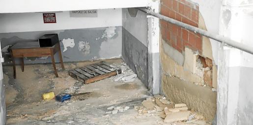 A la derecha, la pared sin reforzar y el boquete que se abrió con la presión del agua, que inundó el aparcamiento.