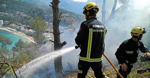 Imagen de archivo de varios bomberos sofocando un incendio en Sóller.