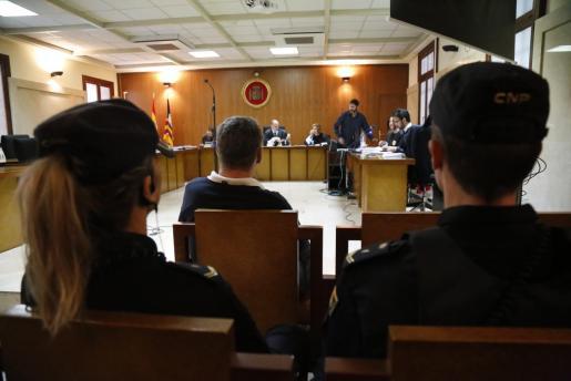 El acusado, custodiado por dos policías, en el juicio celebrado en la Audiencia de Palma.