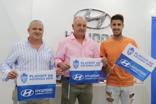 El propietario del concesionario Hyundai Proa Automoción, Joan Pastor, el técnico del Atlético Baleares, Manix Mandiola, y el jugador Alberto Villapalos posan con las banderas que se repartirán este domingo en Son Malferit.