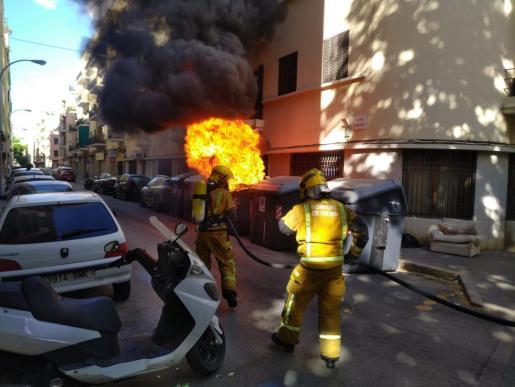 Imagen de los bomberos sofocando el incendio en un contenedor.