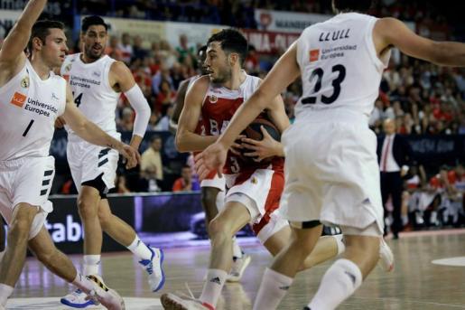 El jugador del Baxi Manresa Sergi García (2-d) entra a canasta entre Fabien Causeur (i), Sergio Llull (d) y Gustavo Ayón (2-i), del Real Madrid, durante el segundo partido de los cuartos de final de la Liga ACB de baloncesto disputado esta noche en el Nou Congost de Manresa.