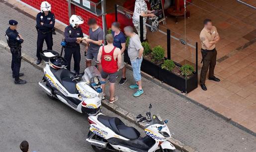 Momento en que los agentes interponen la multa a un turista por comprar un producto de venta ambulante.