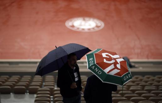 Dos espectadores se cubren de la lluvia con sendos paraguas en una de las pistas del torneo de Roland Garros, este miércoles en París (Francia).