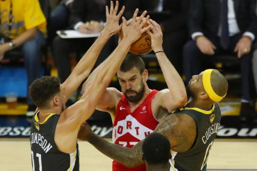 Marc Gasol intenta superar la defensa de Klay Thompson y DeMarcus Cousins.