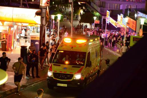 Una ambulancia se lleva a un turista agredido durante un intento de robo. A la izquierda, un grupo de turistas ebrios pasa junto a un supuesto vendedor de color, en la acera.