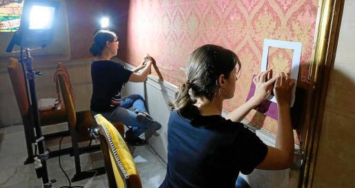 Varias restauradoras trabajan en la recuperación del tapiz que cubre la sala de plenos del Consell de Mallorca.