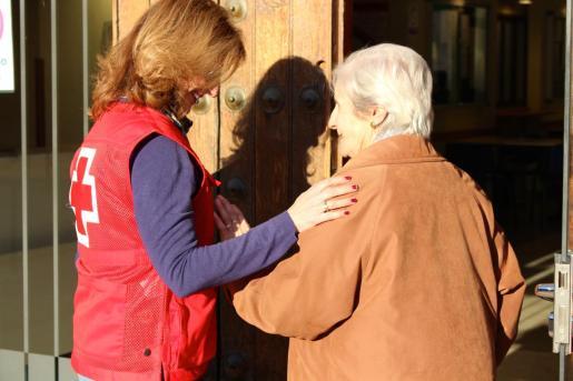 Una Voluntaria de Cruz Roja ayudando a una anciana.