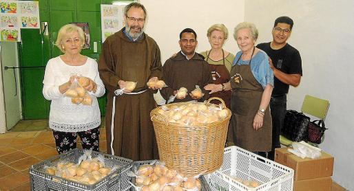 El padre superior, Gil Parès, fray Stephan Baska y los voluntarios, junto a los panes.