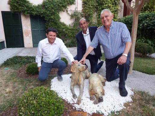 Vicenç Sastre (derecha) con Oscar Mayol y Santiago Mayol junto a las esculturas de sus queridos perros Turc y May.