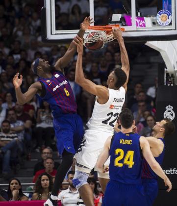 El ala-pívot estadounidense del FC Barcelona Lassa Chris Singleton (i) lucha con Edy Tavares, del Real Madrid, durante el primer partido de la final de la Liga ACB.