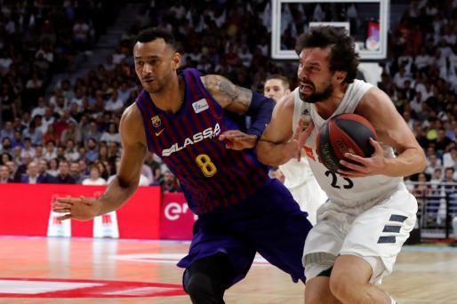 El base del Real Madrid, Sergio Llull controla la pelota ante la oposición del escolta húngaro del Barcelona Lassa, Adam Hanga.