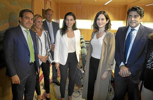 En el centro, las candidatas de Vox y el PP a la Comunidad de Madrid, Rocío Monasterio e Isabel Díaz Ayuso, junto con sus comités negociadores.