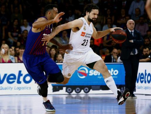 El jugador del Real Madrid Sergio Llull trata de escapar de Adam Hanga, del Barcelona Lassa.